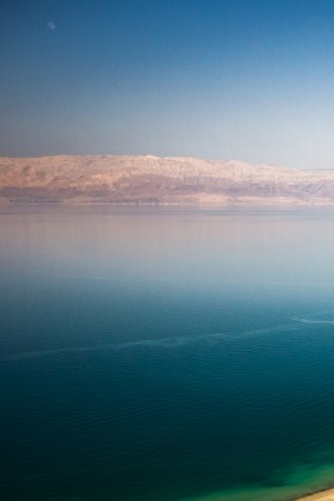 A calm dead sea with in the distance Jordan,the rocks colored red by the evening sun.