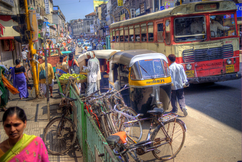 The traffic on the streets of Pune is busy with rickshaws, bicycles, buses and pedestrians.