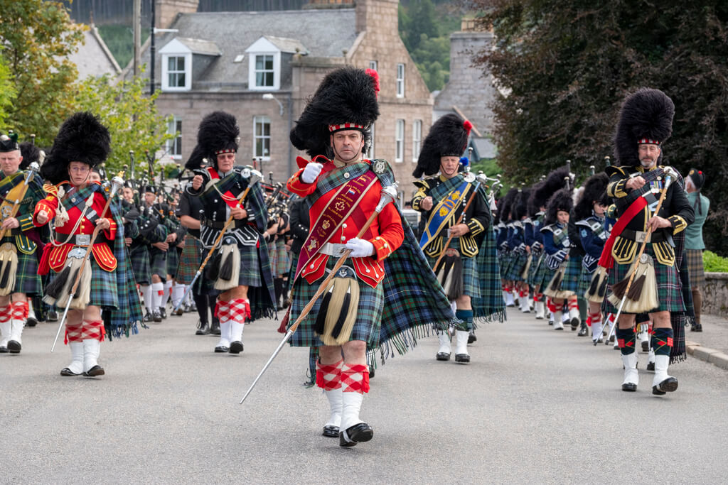 A Pipe band March through Ballater during The Ballater Highland Games