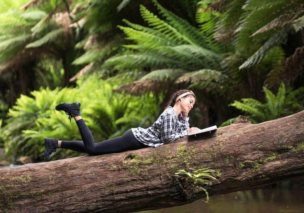 Woman reading book in jungle RF