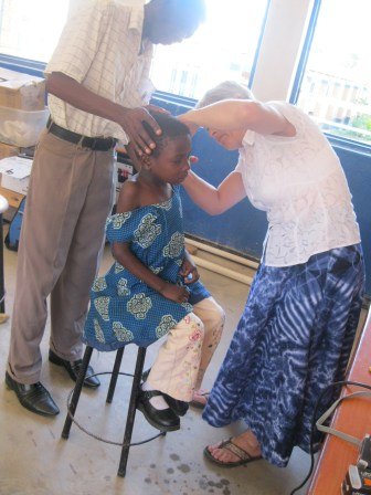 Malita's ears are being checked by an assistant to evaluate whether an hearing aid could help
