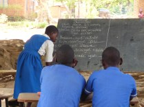 Malita writing at the blackboard