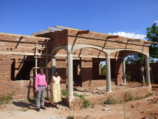 Clement and Grace in front of their new house