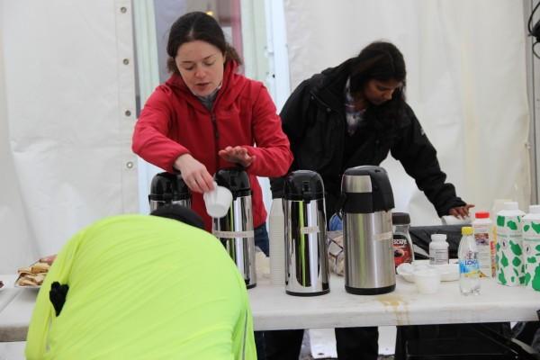 Svetlana häller upp kaffe till en löpare som passar på att fixa skorna. Foto: privat