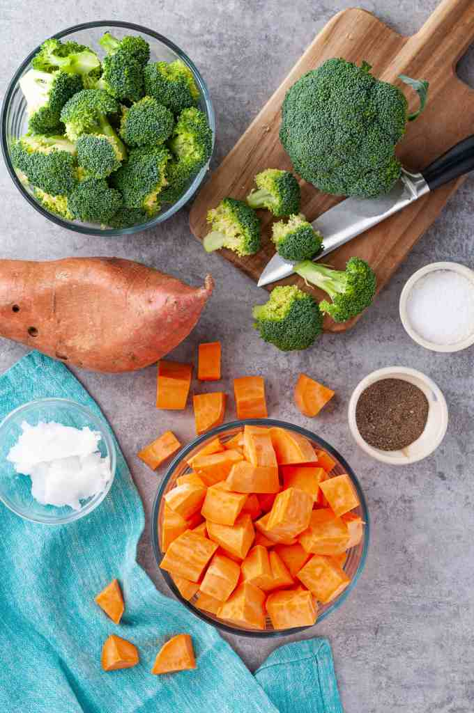 Broccoli, sweet potatoes, salt and pepper and broccoli and knife on cutting board.