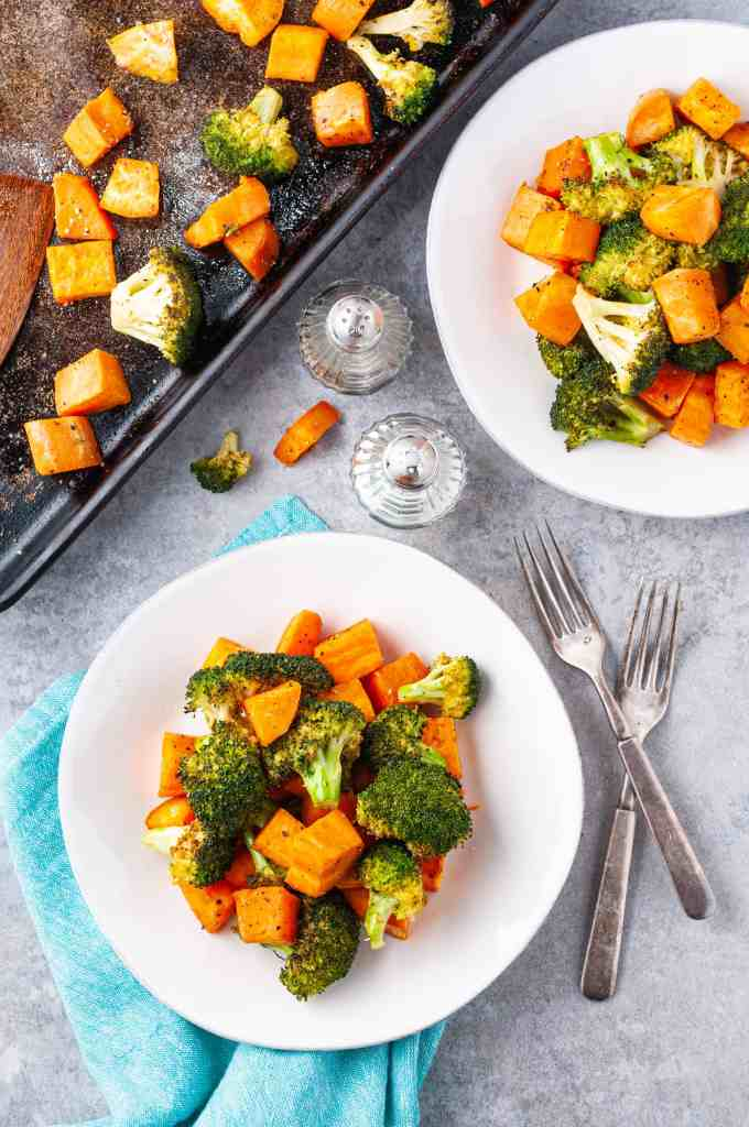 Roasted broccoli and sweet potatoes served on 2 white plates with forks between them in a salt and pepper shakers.