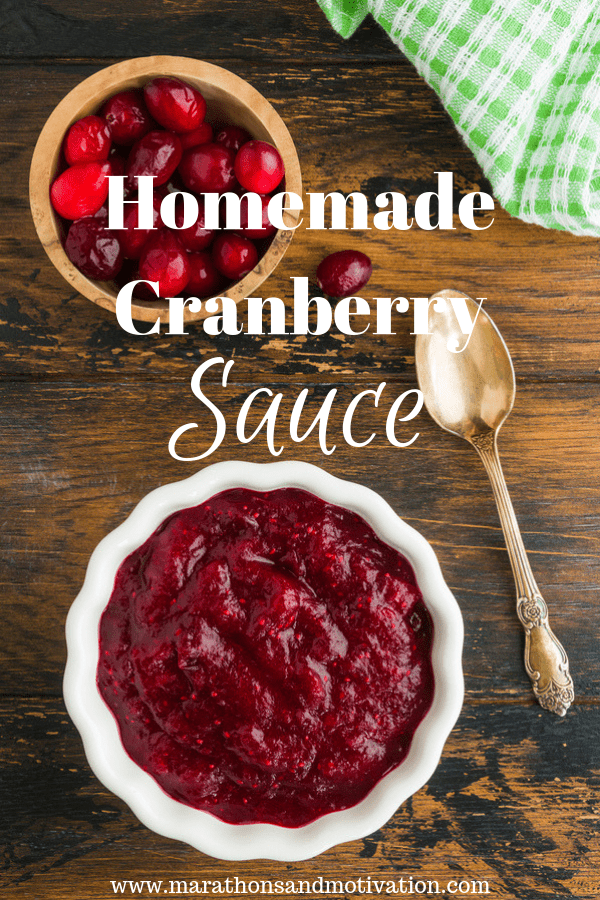Homemade Cranberry Sauce on a wooden slab with fresh cranberries and a spoon