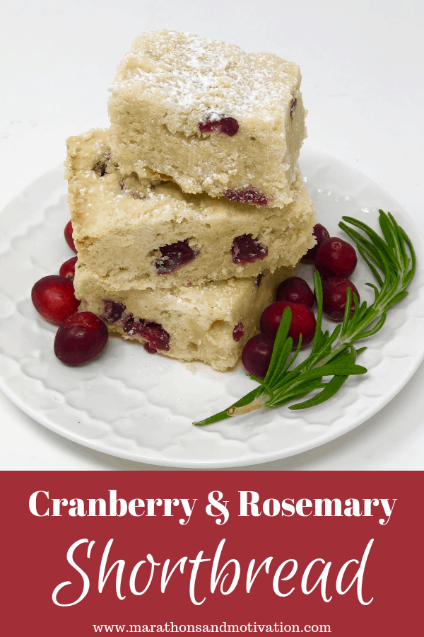 Cranberry and Rosemary Shortbread dusted with confectioner's sugar on a white plate garnished with fresh rosemary and fresh cranberries