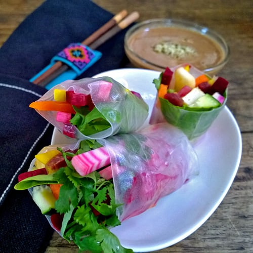 Beet spring rolls with almond sauce on a white plate