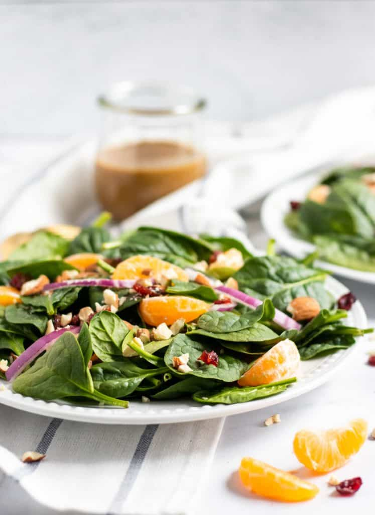 Spinach mandarin salad with honey balsamic background on white plate.