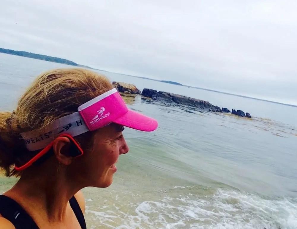 Woman by the ocean wearing headphones and visor