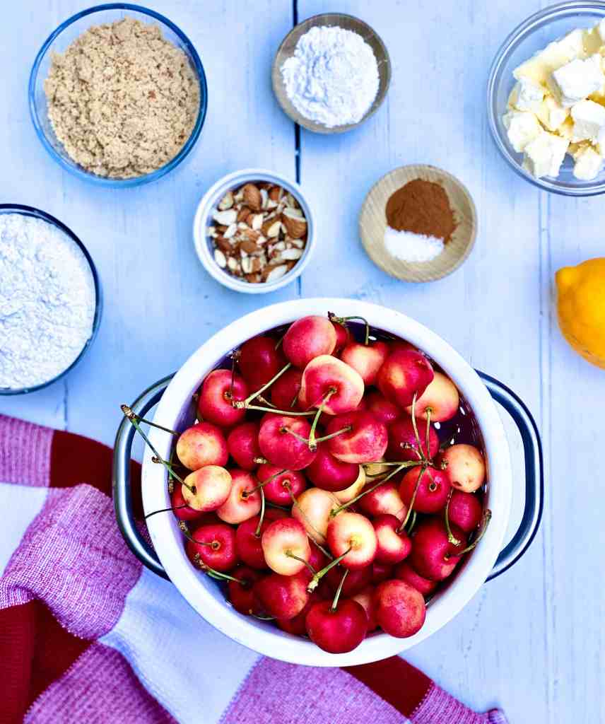 Overhead view of Rainier cherries in a white colander, brown sugar, flour, chopped pecans Arrow Root powder, cinnamon, salt, butter and lemon with a red and white dish towel on the eggs.