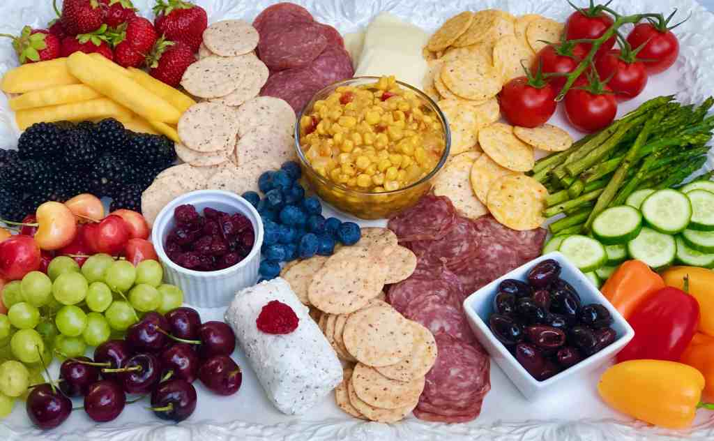 Create the perfect summer charcuterie platter: vegetables, fresh fruit, dried fruit, cheeses, cured meats, olives, salsa