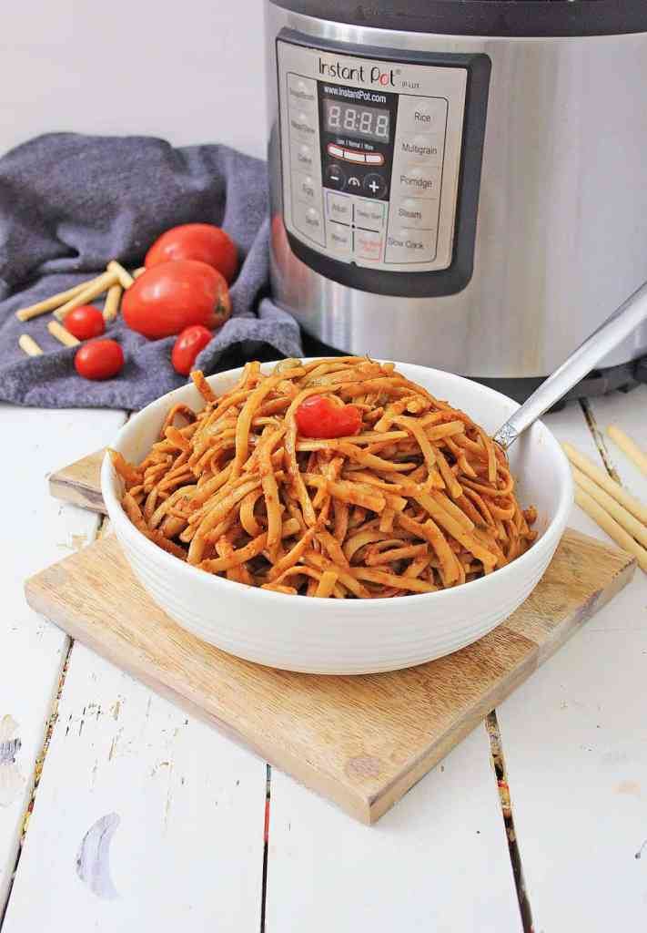 A bowl of Pasta Puttanesca next to an Instant Pot