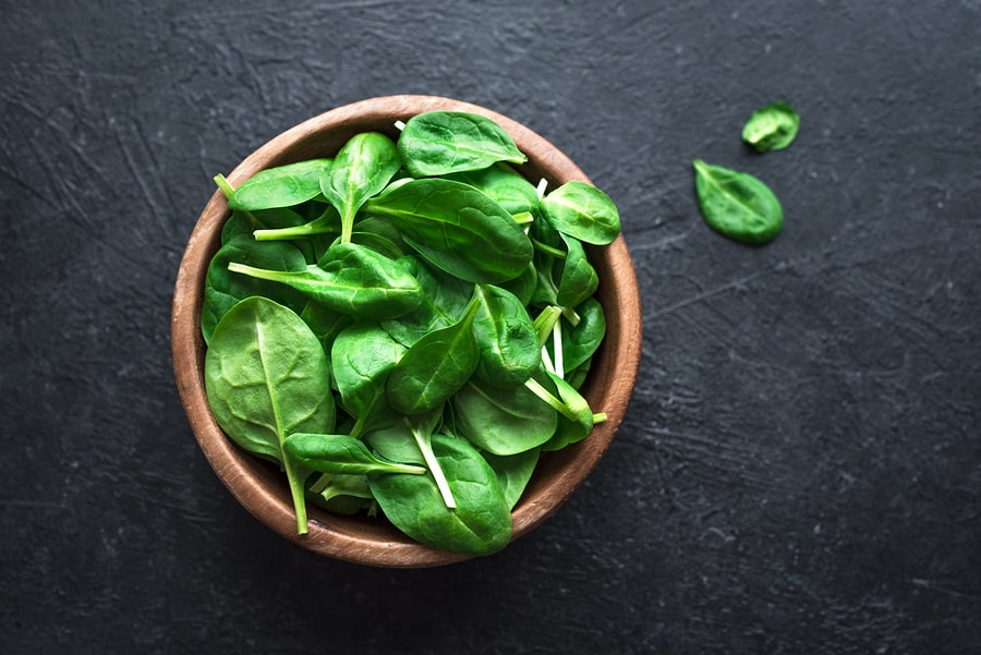 Baby spinach leaves in bowl on black background, top view, copy space. Clean eating, detox, diet food ingredient - green organic spinach.