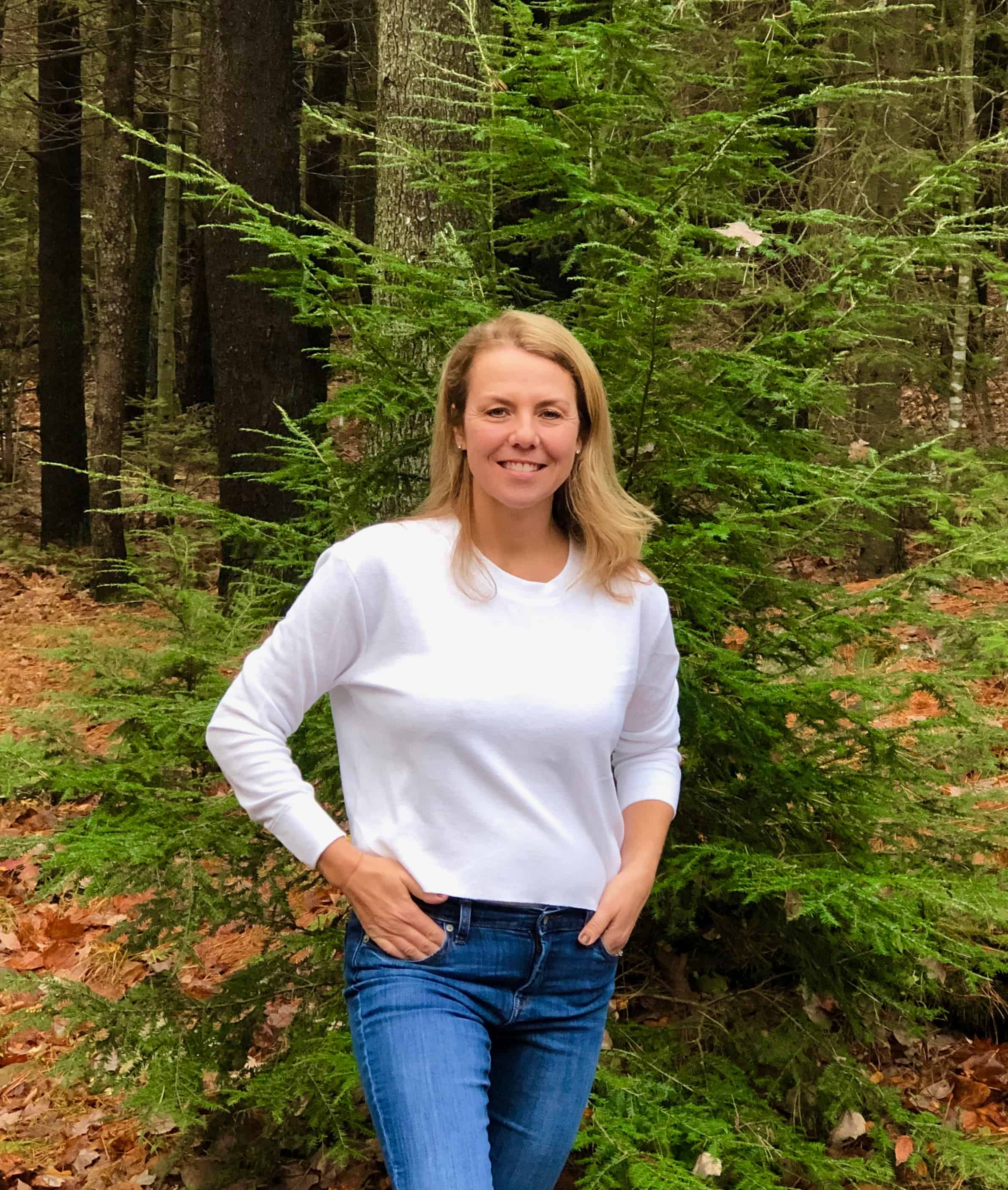 Beautiful blond woman in white thermal crop top and denim jeans standing outside by tree in Maine during the Fall.