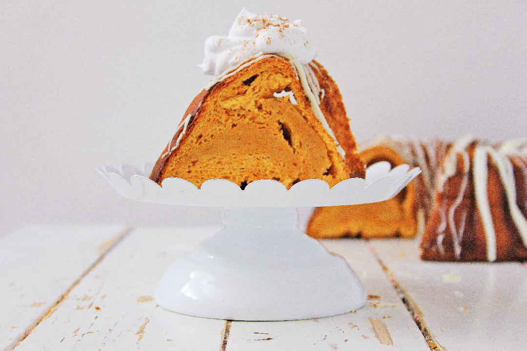 Pumpkin Angel Food Cake on a white cake stand with a white background.