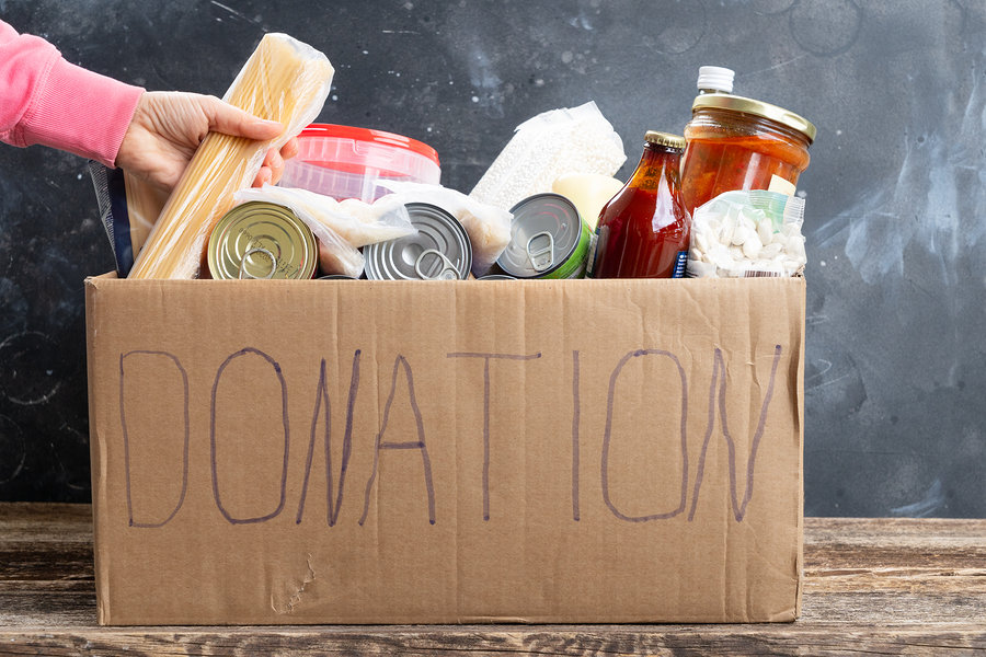 Woman putting food into Donate Box, donation and charity concept