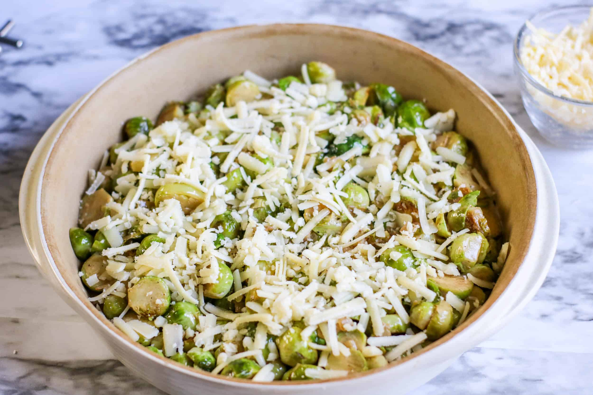Brussels sprouts with cheese in a casserole dish on a white marble background.