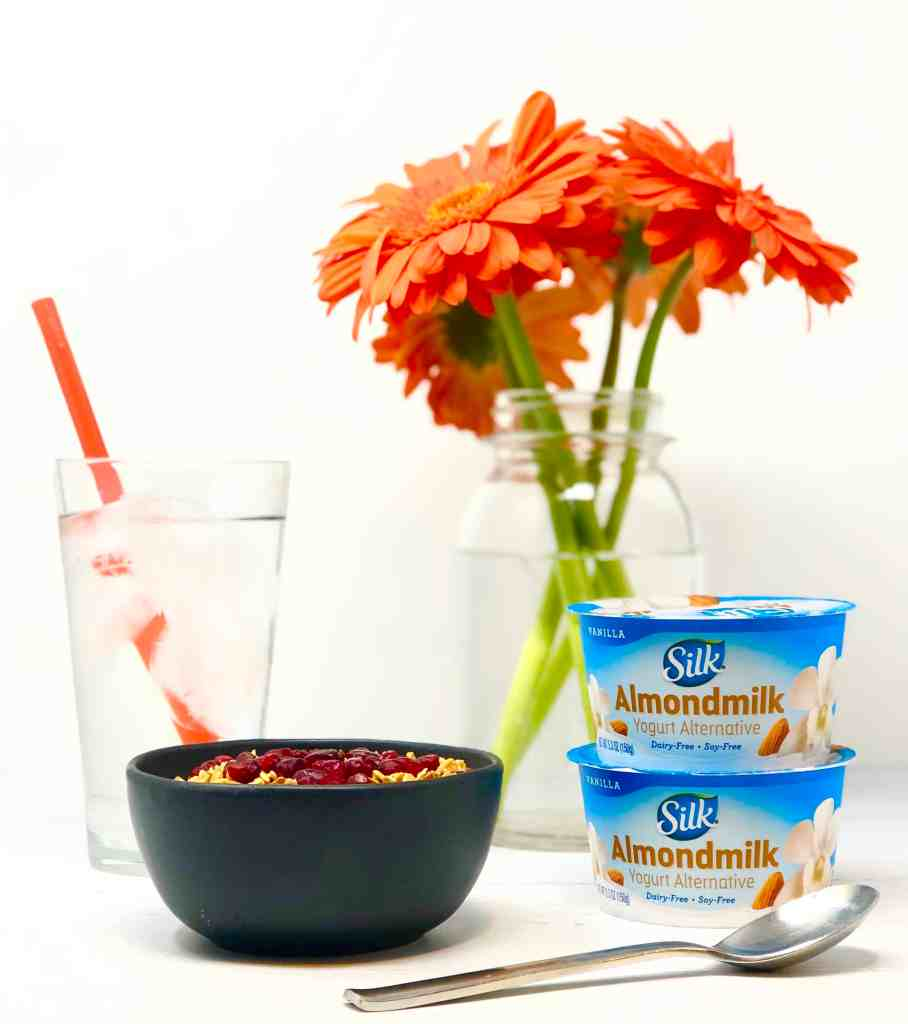 Smoothie bowl, glass of ice water, Silk almond yogurt and orange Gerber daisies on white background.