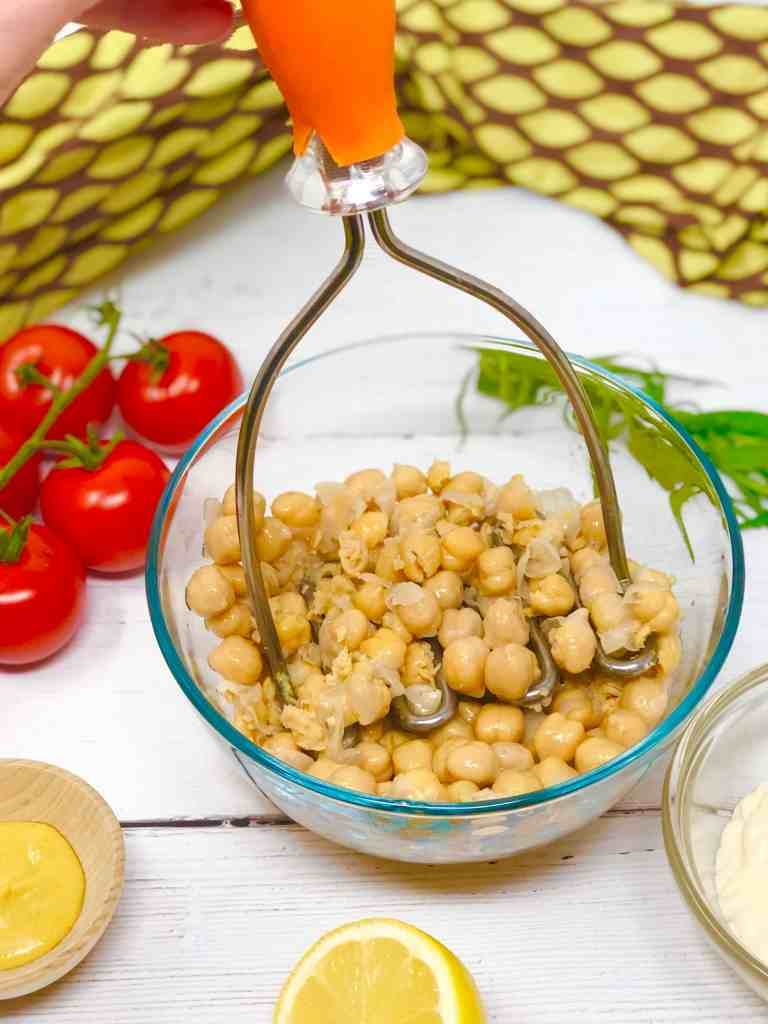 Mashing chickpeas in a glass bowl.