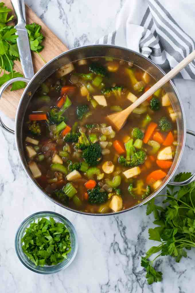 broccoli, carrots, celery, and parsnip in a pot with vegetable stock on a white background with parsley on the side.