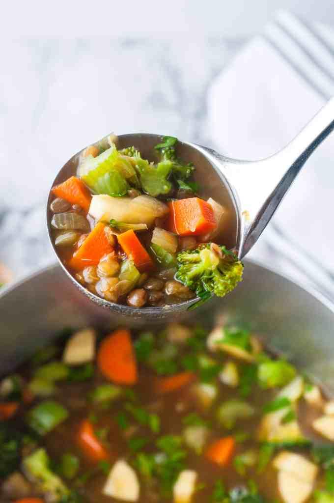 Vegan lentil soup on a serving ladle.