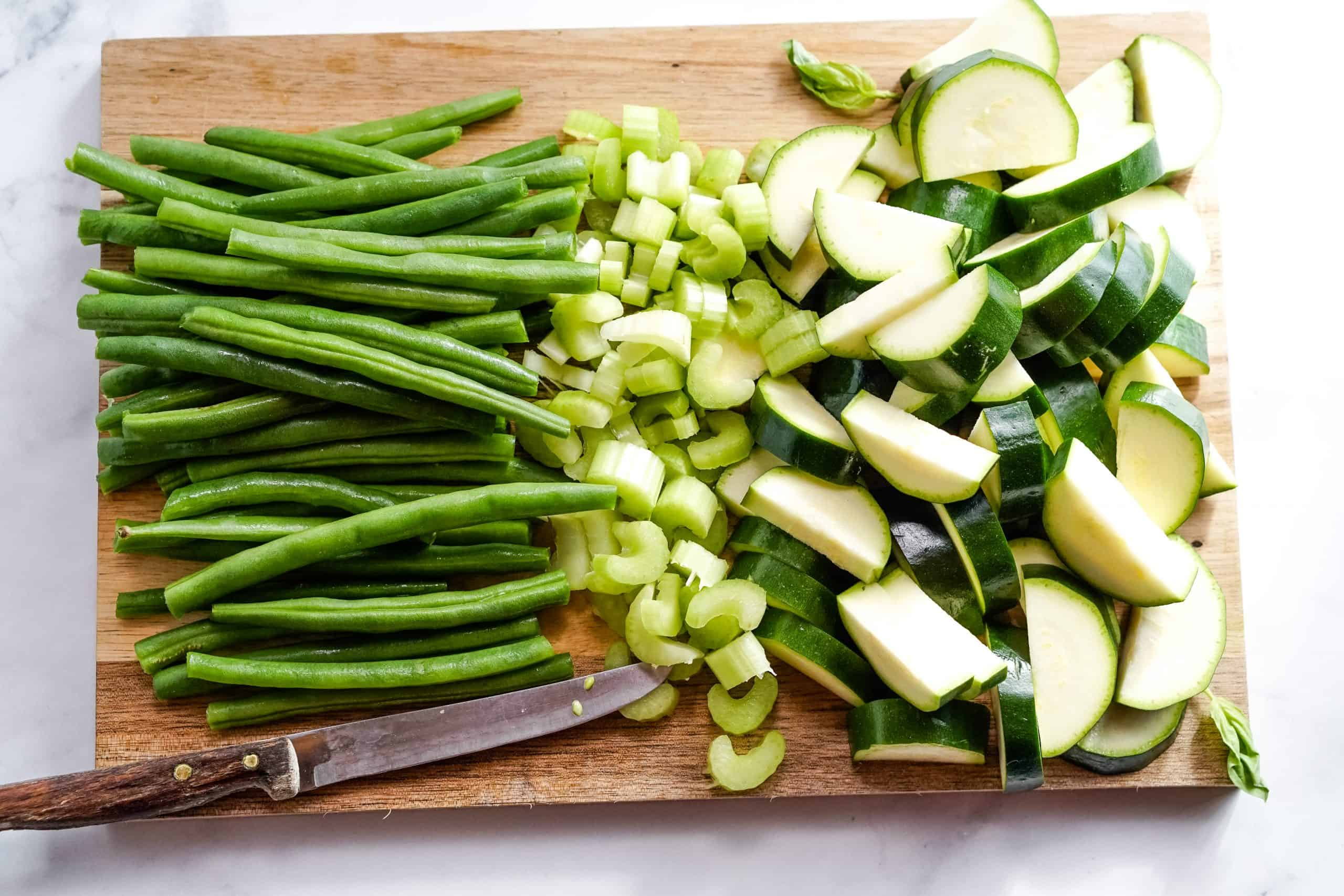 Green beans, chopped celery and zucchini on a cutting board.