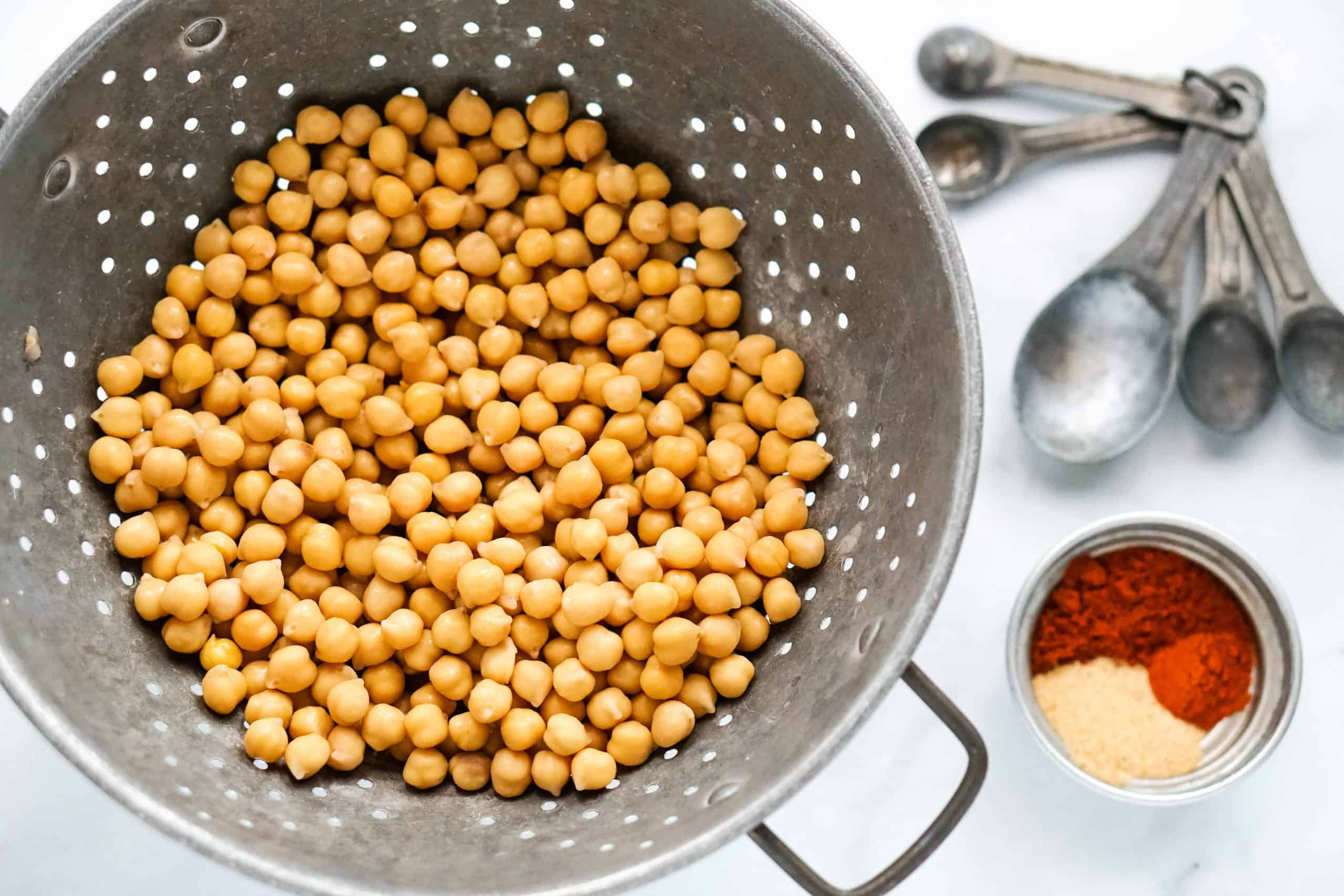 chickpeas in colander, measuring spoons and spices.