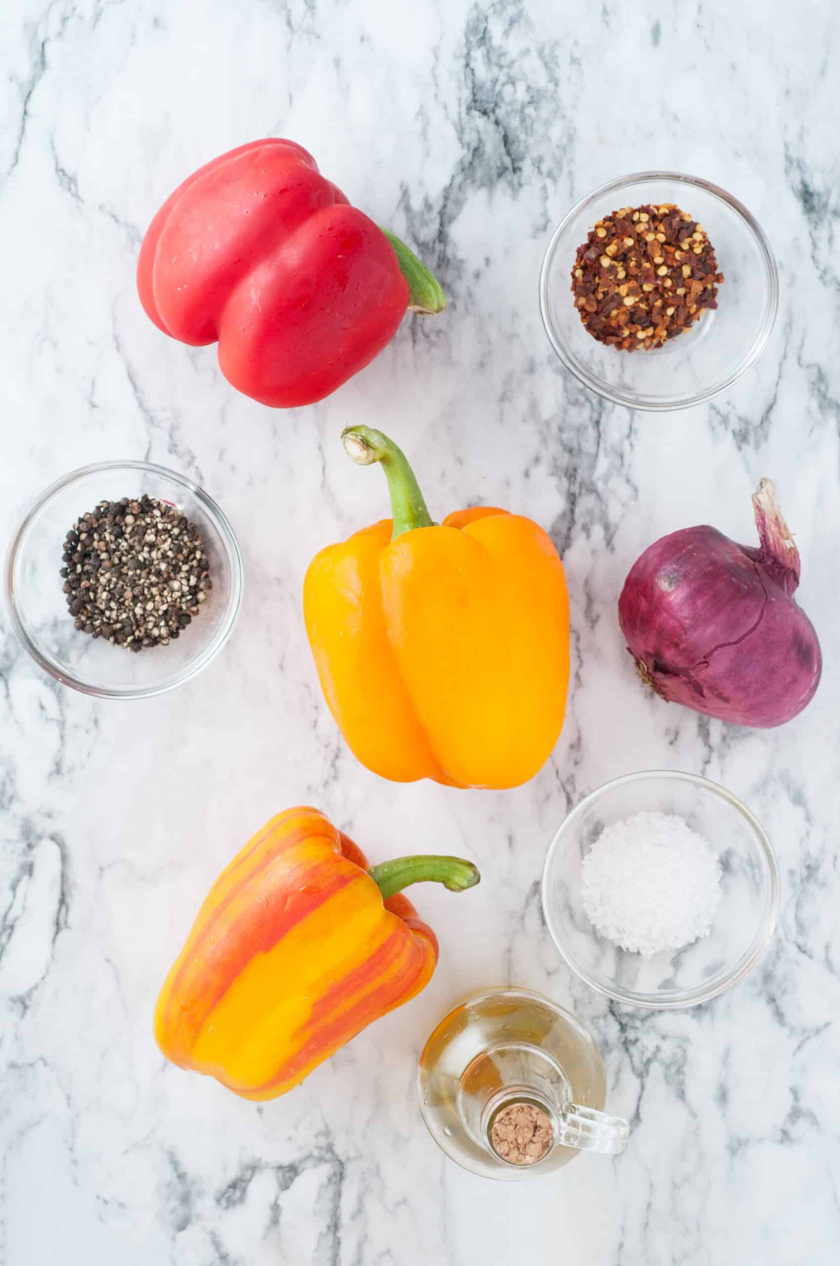 Colored bell peppers, red onion, salt, pepper and crushed red pepper and olive oil on white marble background.
