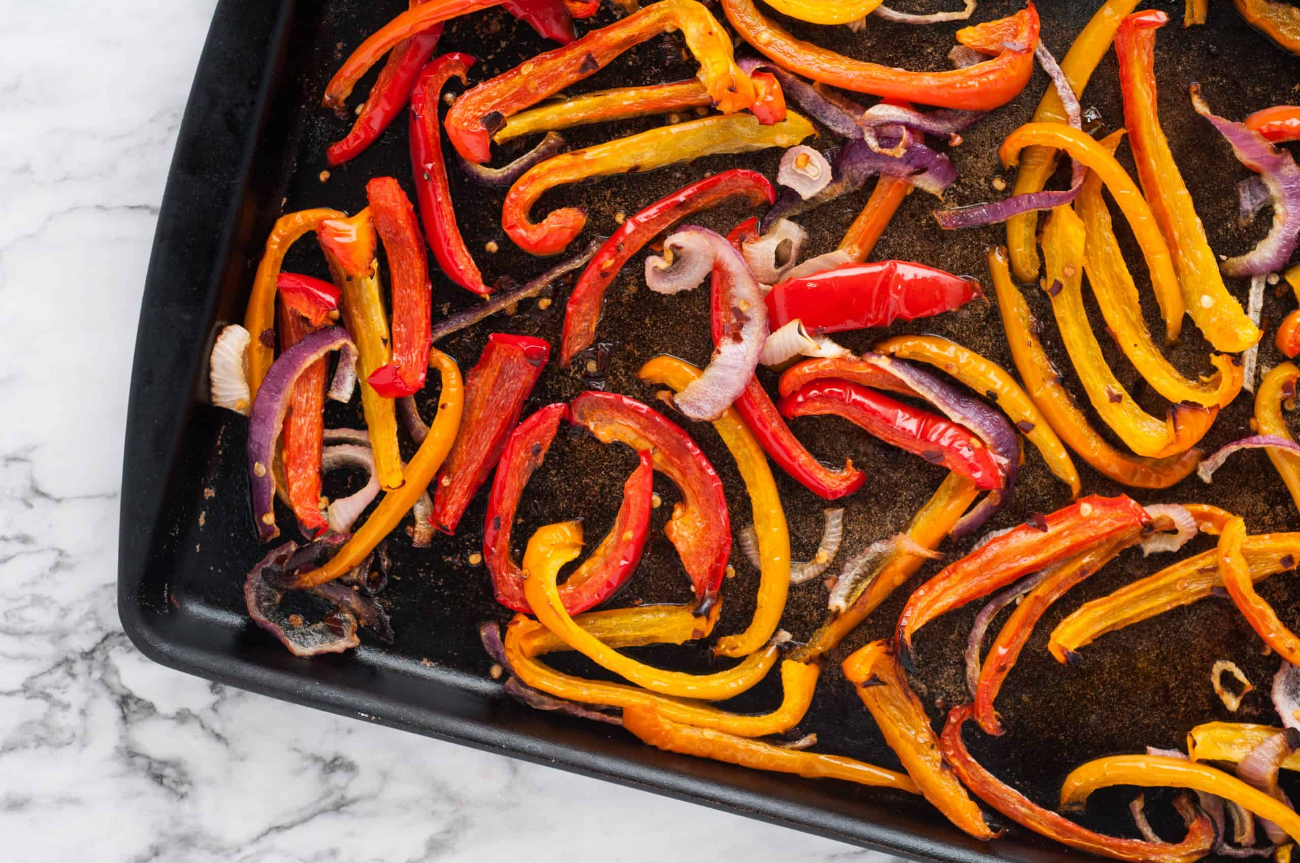 bell pepper strips and onions on a baking sheet.
