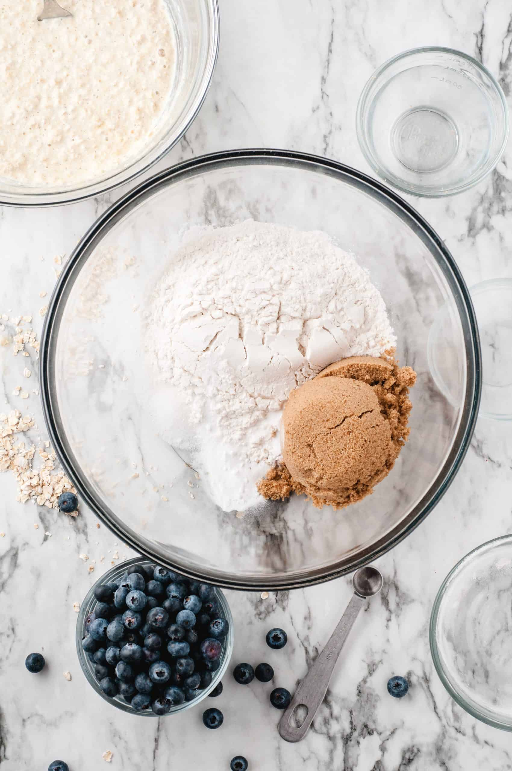 Flour and brown sugar in a glass bowl with blueberries on the side.