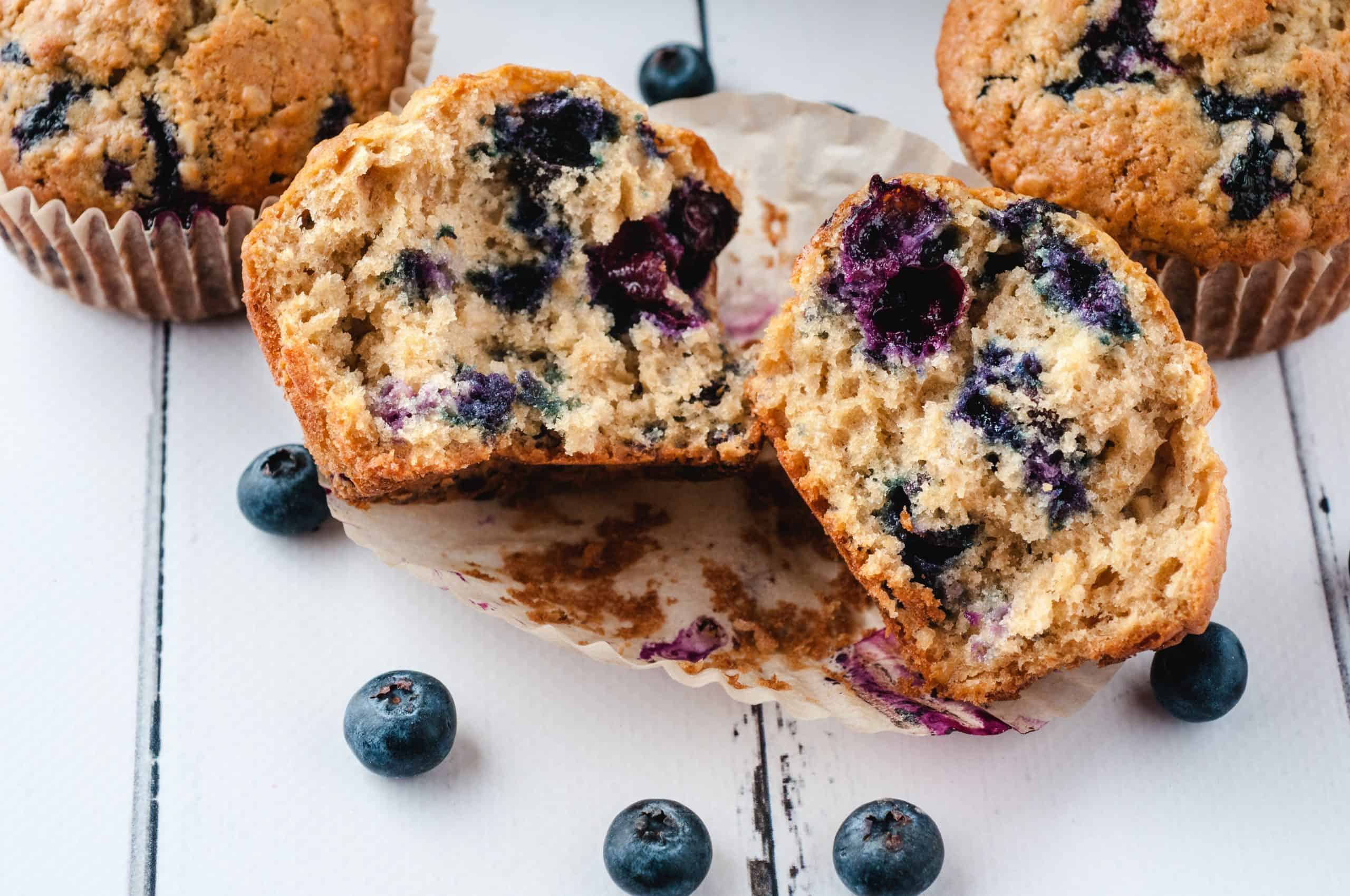 Fresh blueberry muffins with one broken in half on white background.