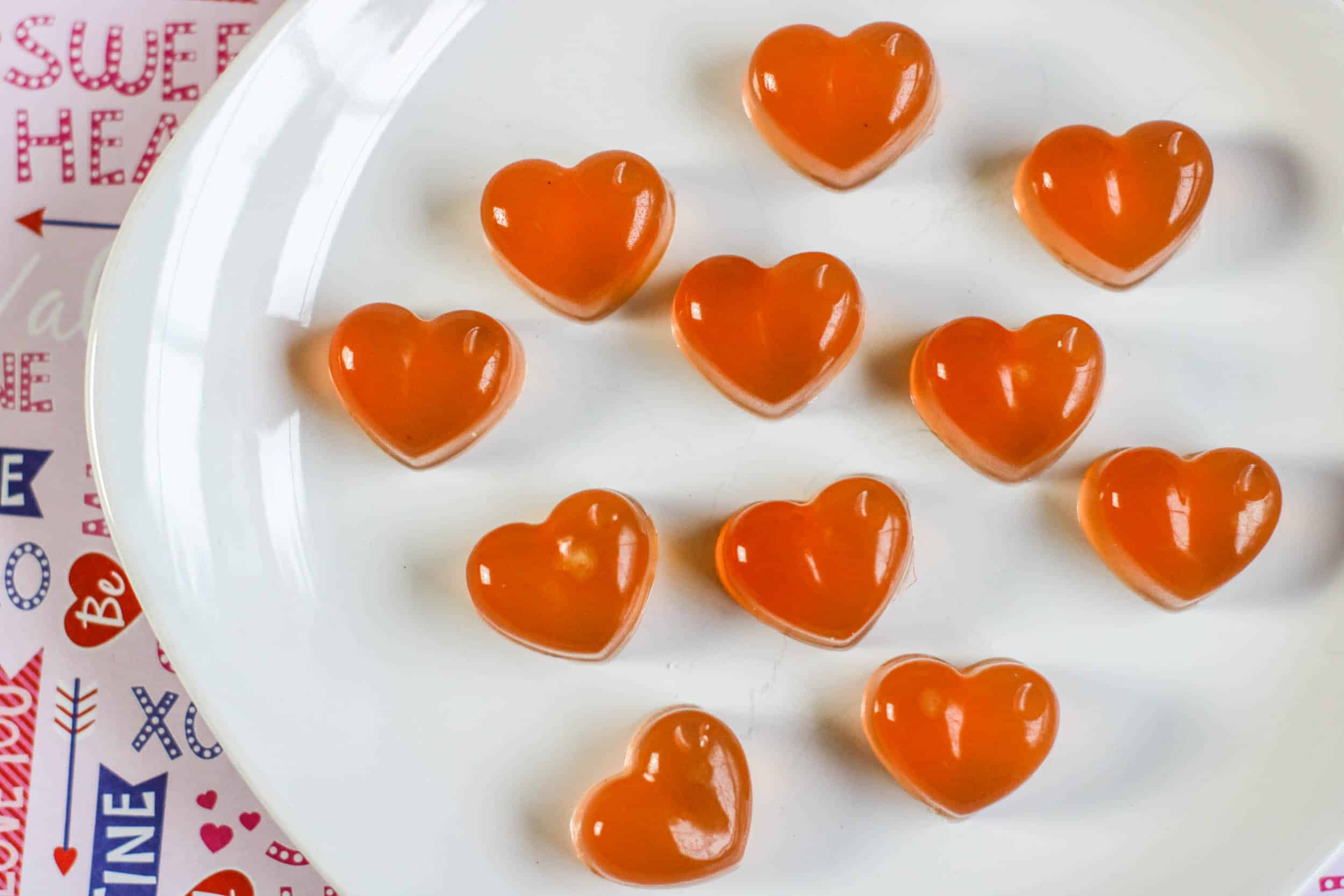 healthy gummie hearts on a white plate.