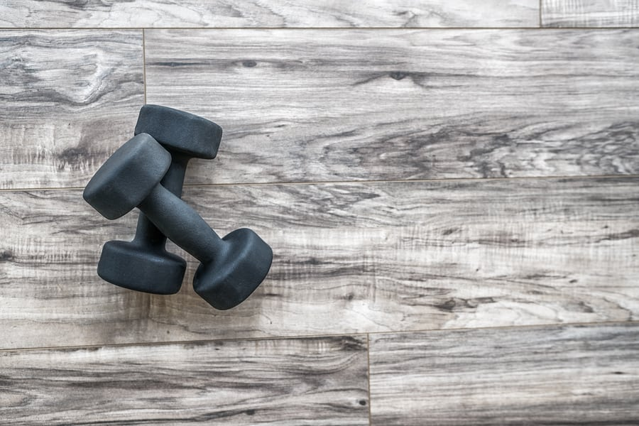 Training at home fitness concept: dumbbell weights on wood floor at fitness gym . Weight loss and health. Sport fit lifestyle.