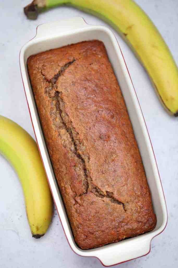 Baked banana bread in a loaf pan with a banana on each side on a white background.