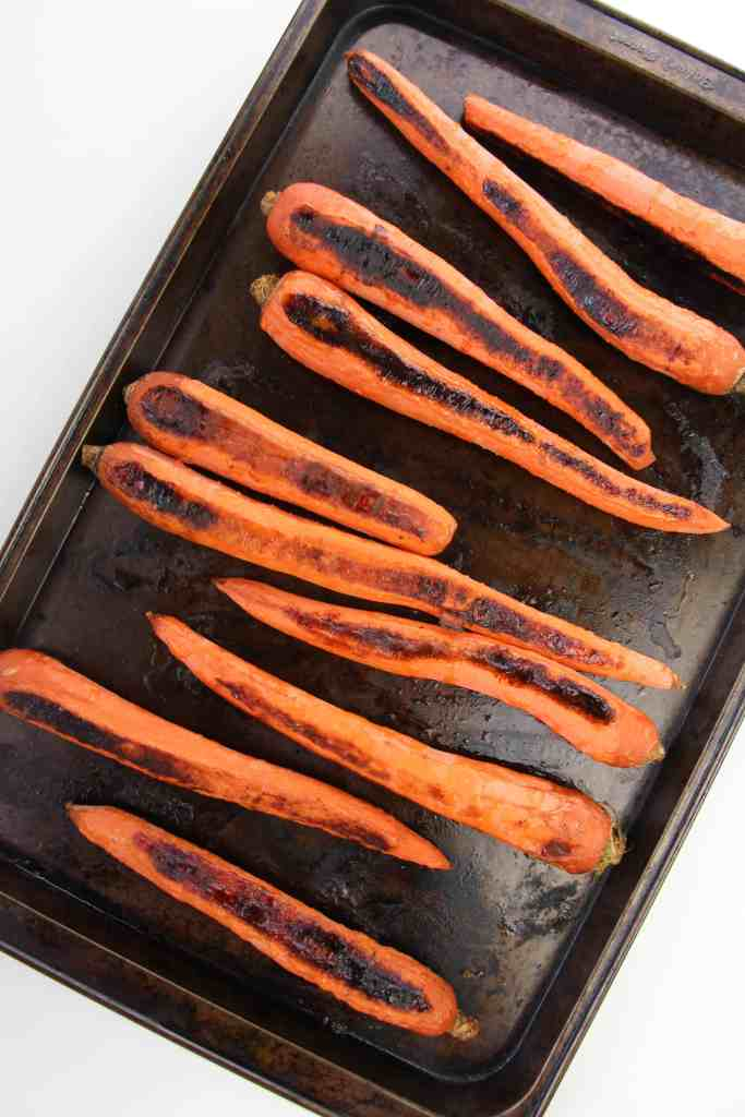 Charred whole carrots on a cookie sheet.
