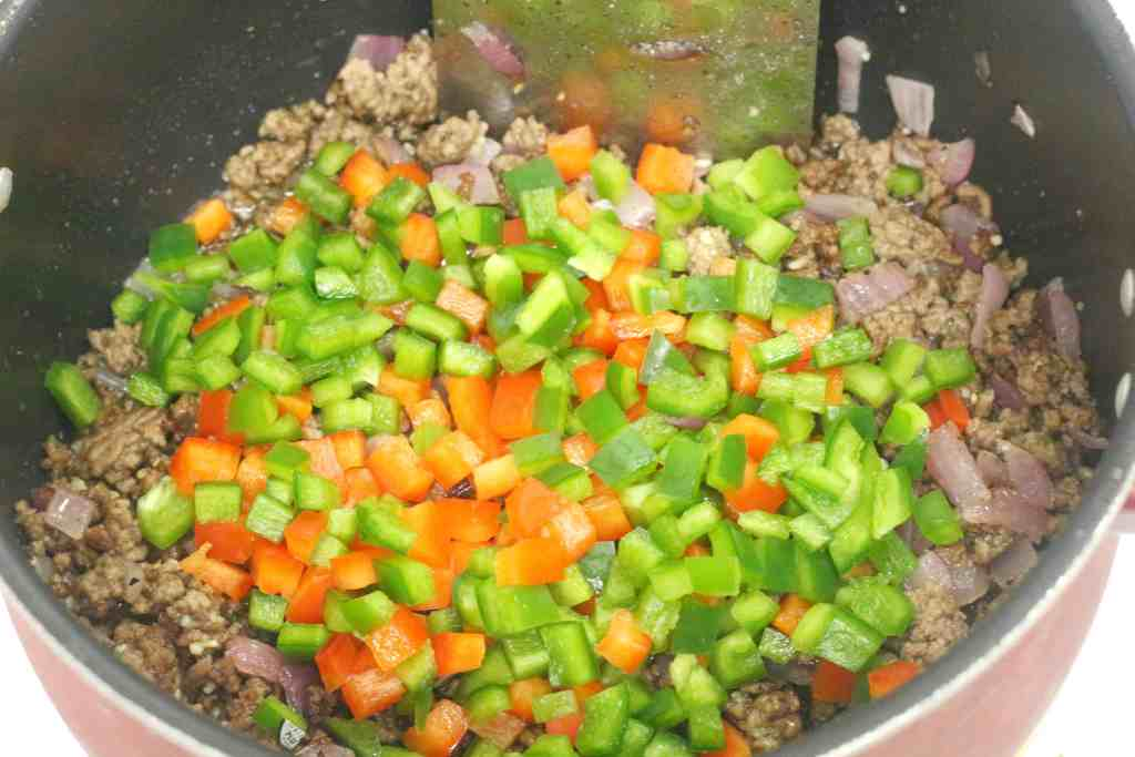 Red and green bell peppers on top of ground beef in a large pot.