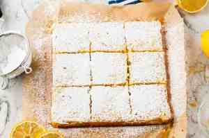 Lemon bars sprinkled with powdered sugar, cut and on top of parchment paper.