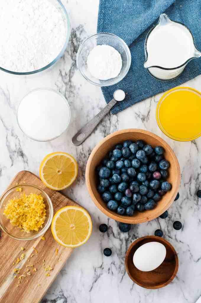 Flour, butter milk, lemon zest, lemon juice, lemon halves, egg and sugar on marble background.