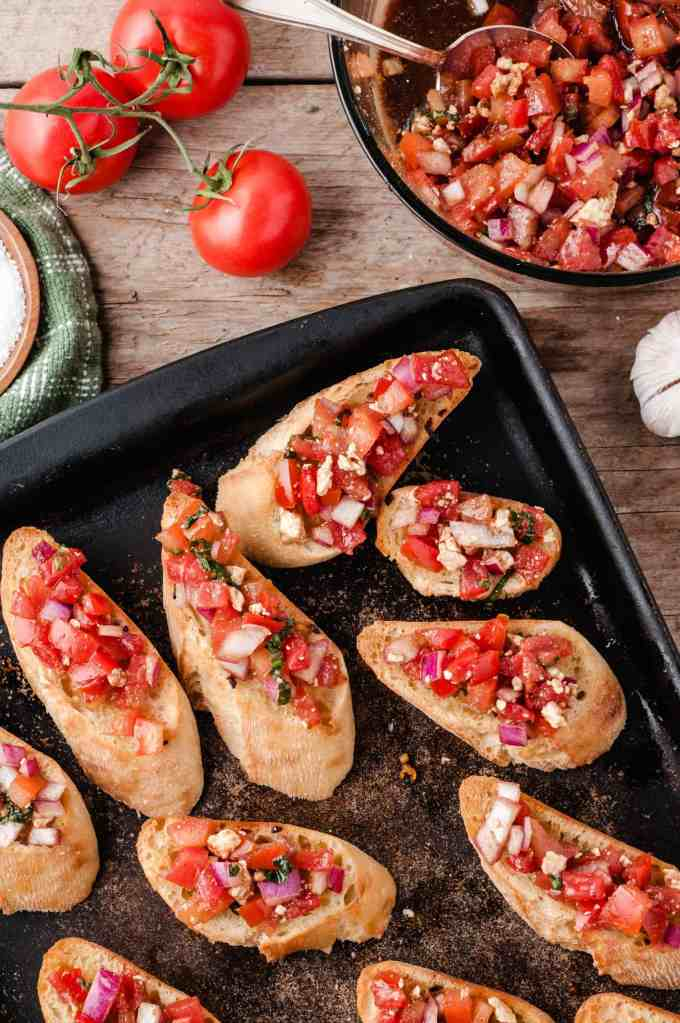 Adding bruschetta topping to baguette slices.