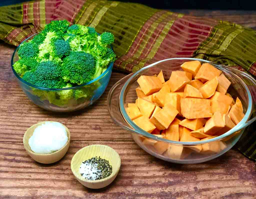 Broccoli and sweet potatoes on a wooden background with coconut oil, salt and pepper.