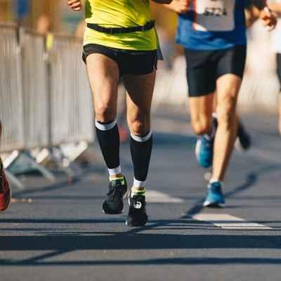 Marathon running race, people feet on autumn road. Runners run urban marathon in the the city