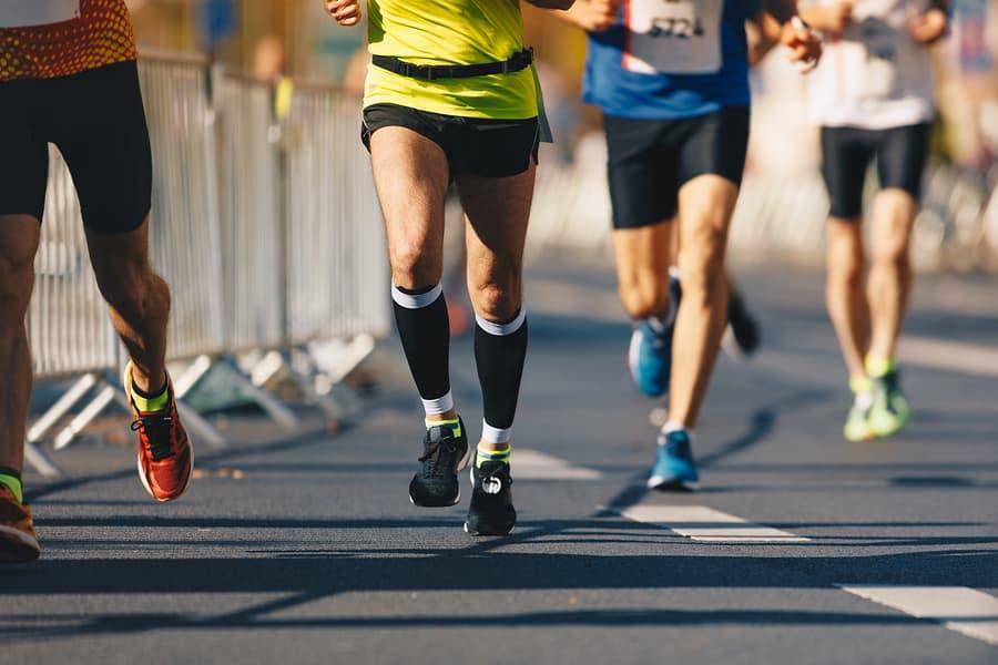 Runner's Quick Guide to Cross-training. Marathon running race, people feet on autumn road. Runners run urban marathon in the the city