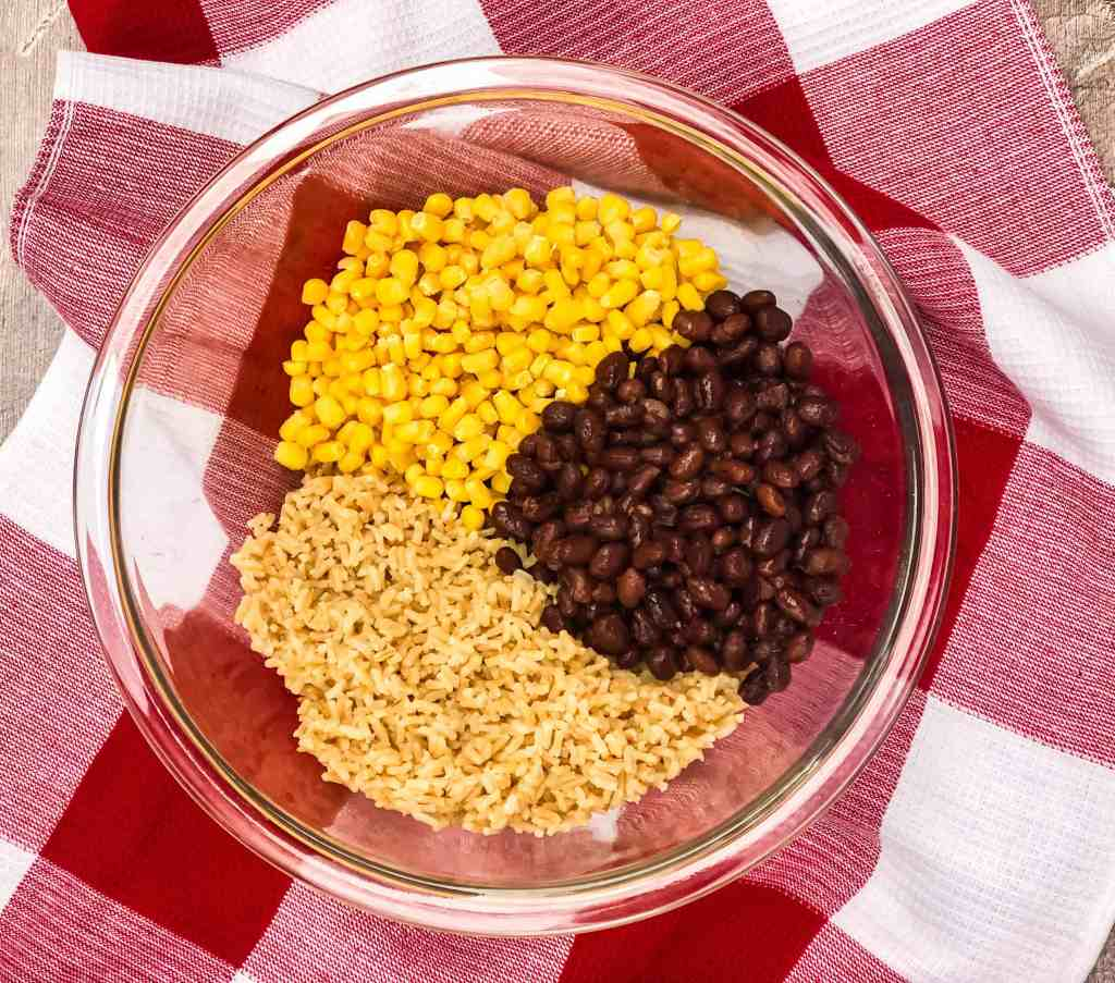 Corn, black beans and brown rice in a glass bowl.
