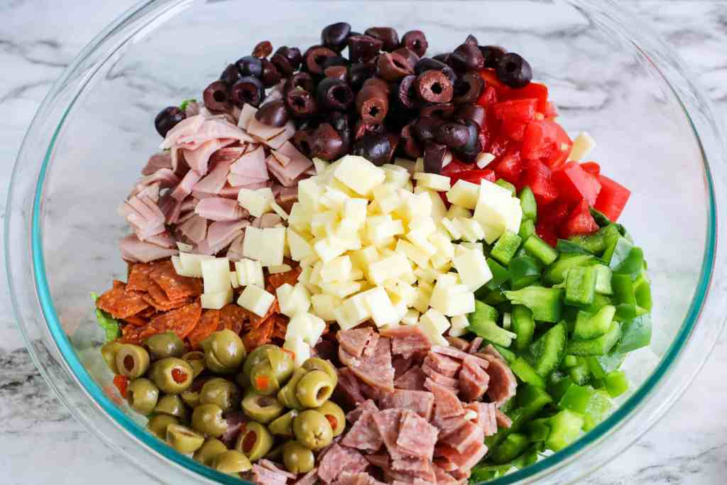 Black olives, green olives, salami, ham, pepperoni, Roma tomatoes and green bell peppers in a large glass bowl on a white marble background.