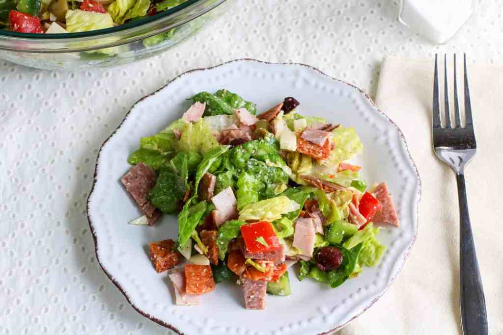 Italian salad on a white plate on a white table cloth with a fork and white napkin.