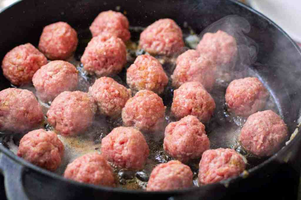 Swedish meatballs cooking in a black iron skillet.