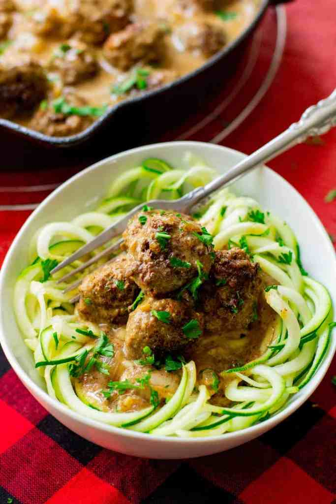 Keto Swedish meatballs over zucchini noodles in a white bowl with a fork in it and a black iron skillet with Swedish meatballs in it behind the bowl.