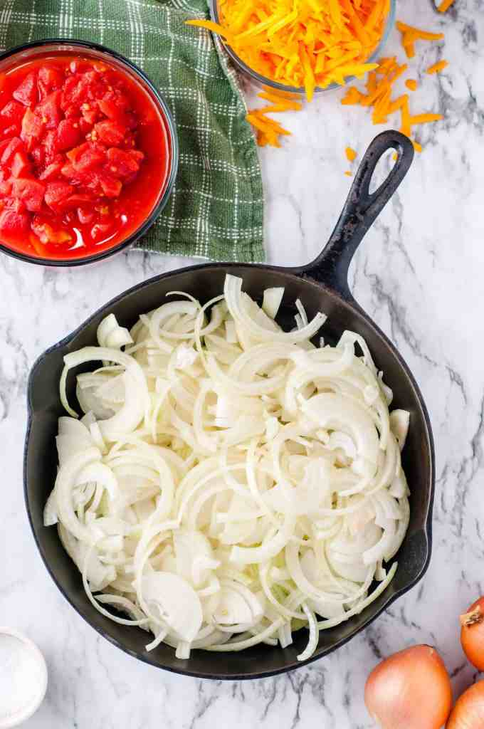 Sliced onions in a cast iron skillet.
